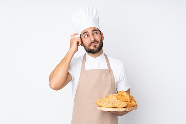 疑いを持って、混乱した表情で白に分離されたいくつかのパンとテーブルを保持している男性のパン屋