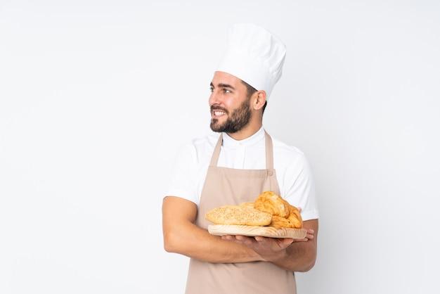 横を見て白で隔離のいくつかのパンとテーブルを保持している男性のパン屋