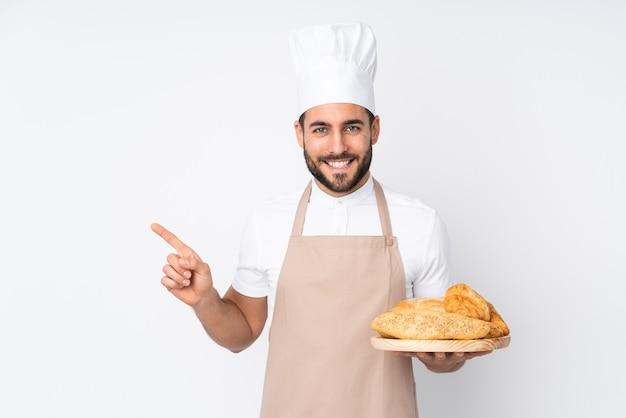 横に白い人差し指で分離されたいくつかのパンとテーブルを保持している男性のパン屋