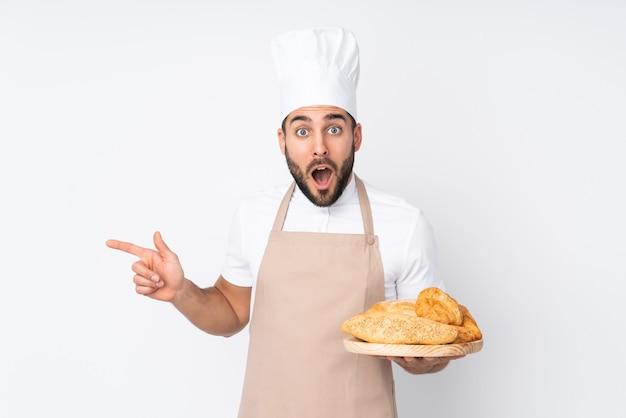 白い壁に隔離されたいくつかのパンとテーブルを保持している男性のパン屋は驚いて、人差し指を横に向けています