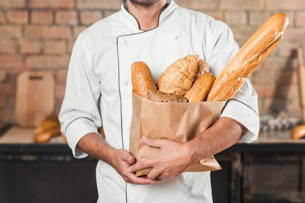 Panettiere maschio che tiene sacchetto di carta con pagnotta di pane diversa