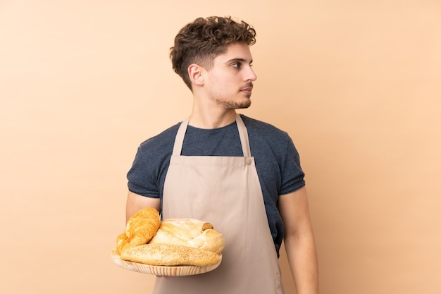 Male baker holding a table with several breads isolated on beige looking side