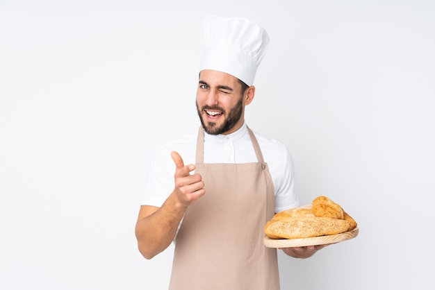 Male baker holding a table with several breads isolated on white wall points finger at you