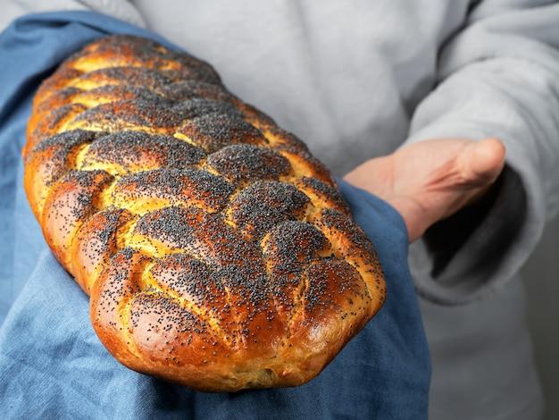 남성 베이커는 전통적인 달콤한 challah 유대인 빵을 보유하고 있습니다.