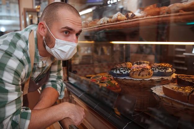 彼のパン屋で小売店のディスプレイを見ている医療フェイスマスクの男性のパン屋