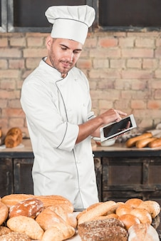 Male baker looking at assortment of breads using digital tablet