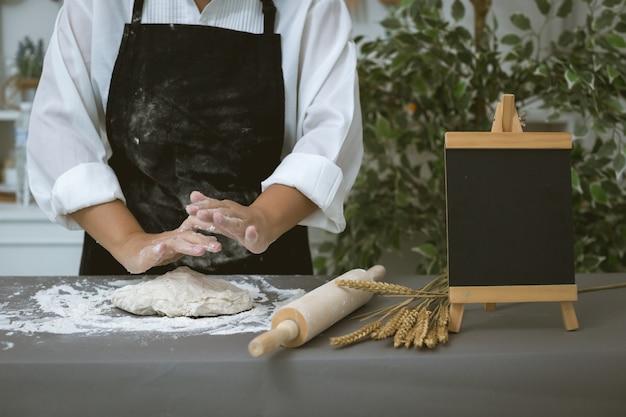 Male baker prepares bread with flour
