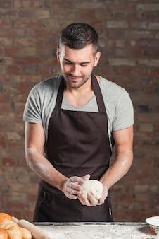 Мужской пекарь готовит хлеб в пекарне