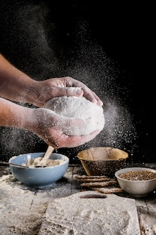 Male baker's hand dusting dough with flour
