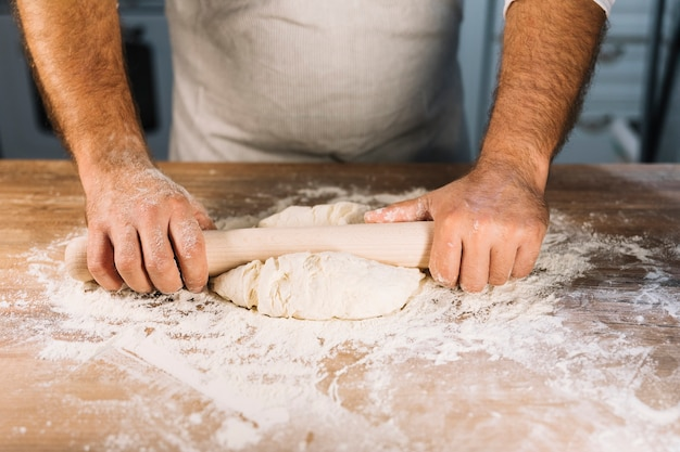 Male baker's hand flattening dough with rolling pin on wooden table