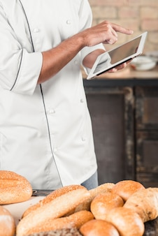 Male baker standing behind the table with breads using digital tablet
