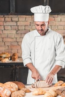 Male baker in uniform cutting bread slice on table