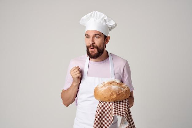 Мужской пекарь со свежим хлебом в руках готовит выпечку