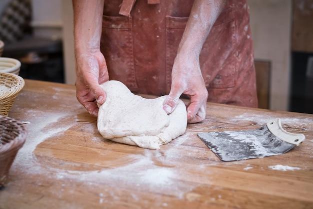 Мужские пекари руки рабочие хлебное тесто с мукой на деревянном столе