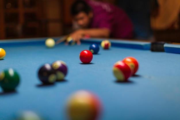 テーブルを狙ってキューを持つ男性のボールプレイスヌーカービリヤードプレーヤー