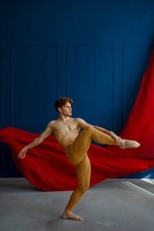 男性バレエダンサー、ダンススタジオでのバランス運動、青い壁と赤い布。筋肉質な体、優雅で優雅な動きのパフォーマー