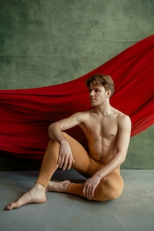 Male ballet dancer, dancing studio, grunge wall and red cloth on background