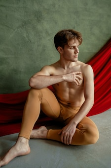 Male ballet dancer, dancing studio, grunge wall and red cloth. performer with muscular body, grace and elegance of movements