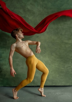 Male ballet dancer doing exercise in dancing studio, grunge wall and red cloth on background