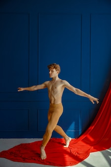Male ballet dancer, performing in action, dancing studio, blue wall and red cloth. performer with muscular body, grace and elegance of dance