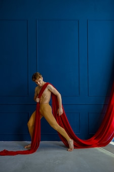 Male ballet dancer performing with red cloth in dancing studio, blue walls. performer with muscular body, grace of movements