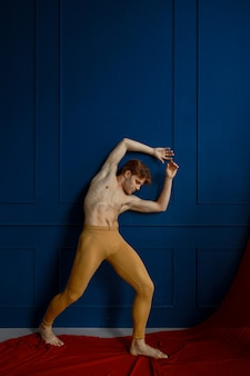 Male ballet dancer poses at blue wall in dancing class, red cloth. performer with muscular body, grace and elegance of movements
