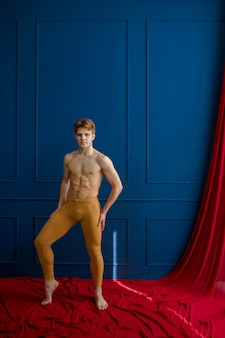 Male ballet dancer poses in dancing studio, blue walls and red cloth on background