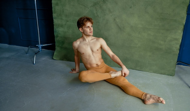 Male ballet dancer sittiing on the floor in dancing class, grunge wall on background