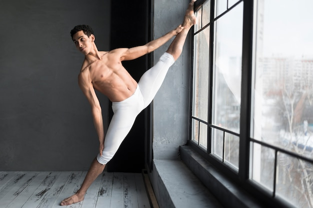 Male ballet dancer stretching next to window