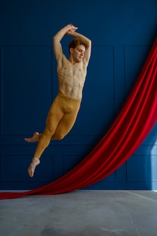 Male ballet dancer, training in dancing class, blue walls and red cloth on background