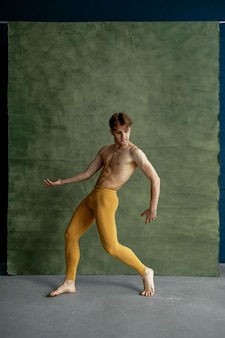 Male ballet dancer, training in dancing class, grunge wall. performer with muscular body, elegance of movements