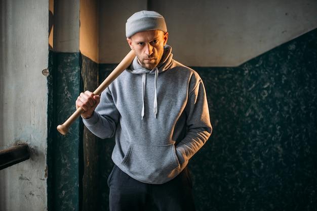 Мужчина-бандит с бейсбольной битой стоит у входа. уличный грабитель ждет жертву. понятие преступления, опасность нападения грабежа