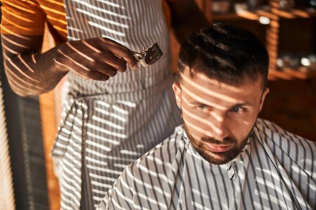 ヴィンテージのバリカンでクライアントの髪を切る男性の理髪師