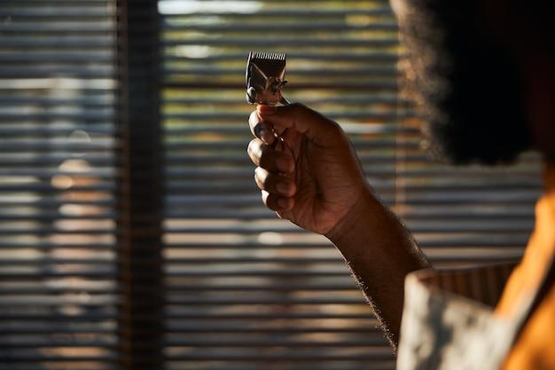 ヴィンテージポータブルヘアトリマーを持っている男性の床屋の手