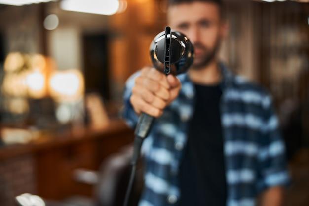 銃のようなヘアドライヤーを保持している男性の床屋