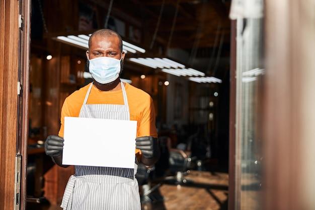 빈 카드 템플릿을 들고 의료 마스크에 남성 이발사