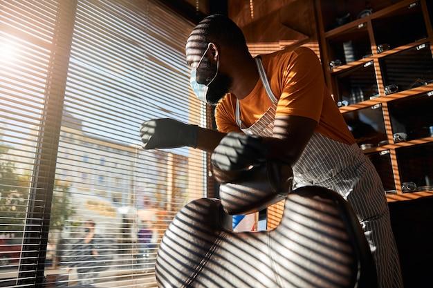 Мужской парикмахер в медицинской маске, глядя в окно в парикмахерской