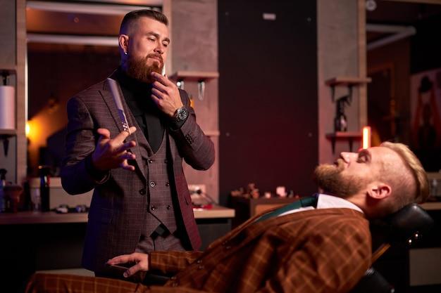 Мужчина-парикмахер готов разрезать своего клиента, сидящего на стуле в строгом костюме