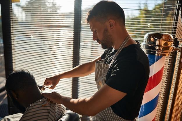 ヴィンテージのバリカンで散髪をする男性の床屋