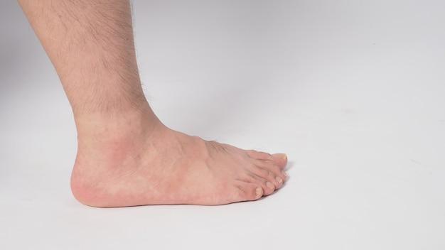 男性の裸足は白い背景で隔離されます。