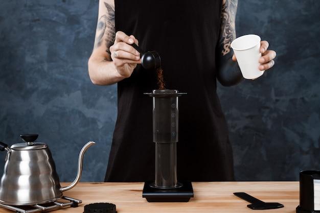 Male barista brewing coffee. alternative method aeropress.