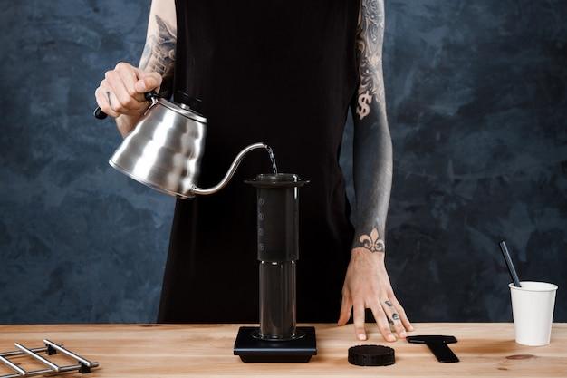 Мужской бариста заваривает кофе. альтернативный метод аэропресс.