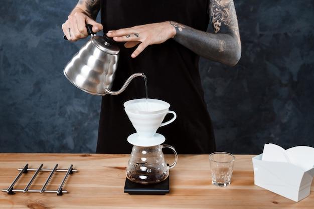 남성 바리 스타 양조 커피. 대체 방법이 쏟아집니다.