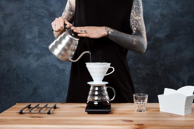 Мужской бариста заваривает кофе. альтернативный метод залить.