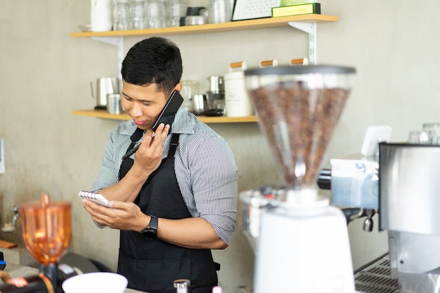 Male barista calling using smartphone