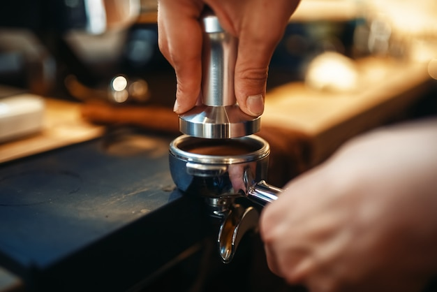 Male barista hands, fresh black coffee preparation