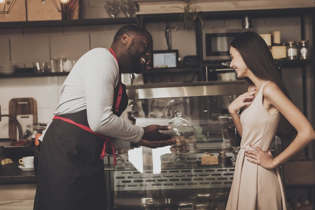 Male barista helps a girl to choose a dessert