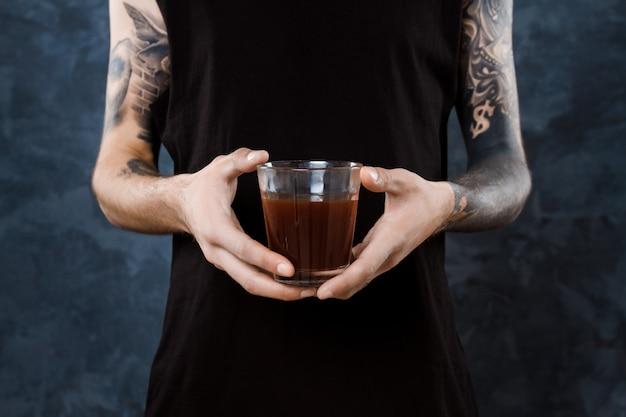 Male barista holding glass with coffee over grey.
