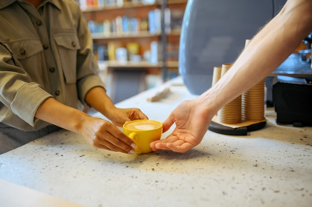 Бариста-мужчина в фартуке дает кофе женщине в кафе
