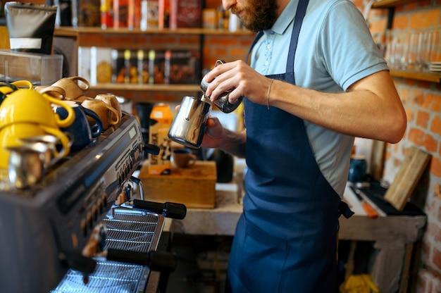 Мужской бариста в фартуке готовит ароматный кофе в кафе